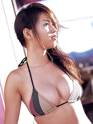 Big breasted asian beauty shows off her busty boobs in a bikini