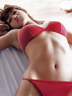 Beautiful asian girl having fun at the beach in a bikini